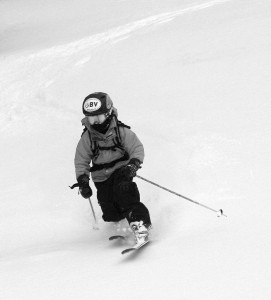 A black and white image of Ty Telemark skiing in powder on the Wilderness Lift Line trail at Bolton Valley Resort in Vermont