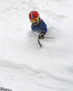 An image of Dylan skiing in powder snow above his waist in the Hayride Trees at Stowe Mountain Resort in Vermont