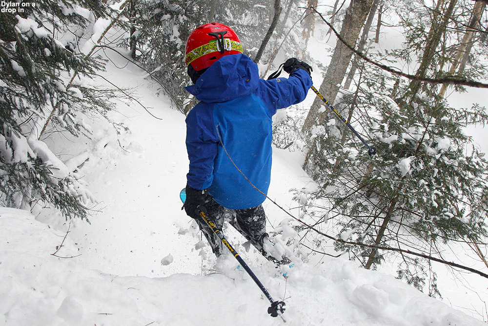 An image of Dylan dropping off a cliff into the powder while skiing at Bolton Valley Resort in Vermont