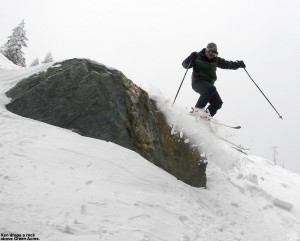 An image of Ken jumping off a rock on skis into the powder above Green Acres at Stowe Mountain Resort in Vermont