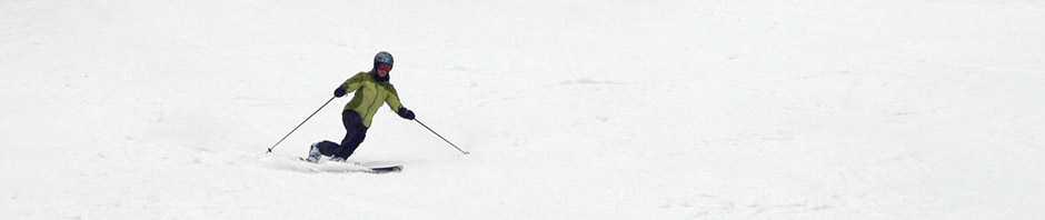 A landscape orientation image of E Telemark skiing in spring snow at Stowe Mountain Resort in Vermont