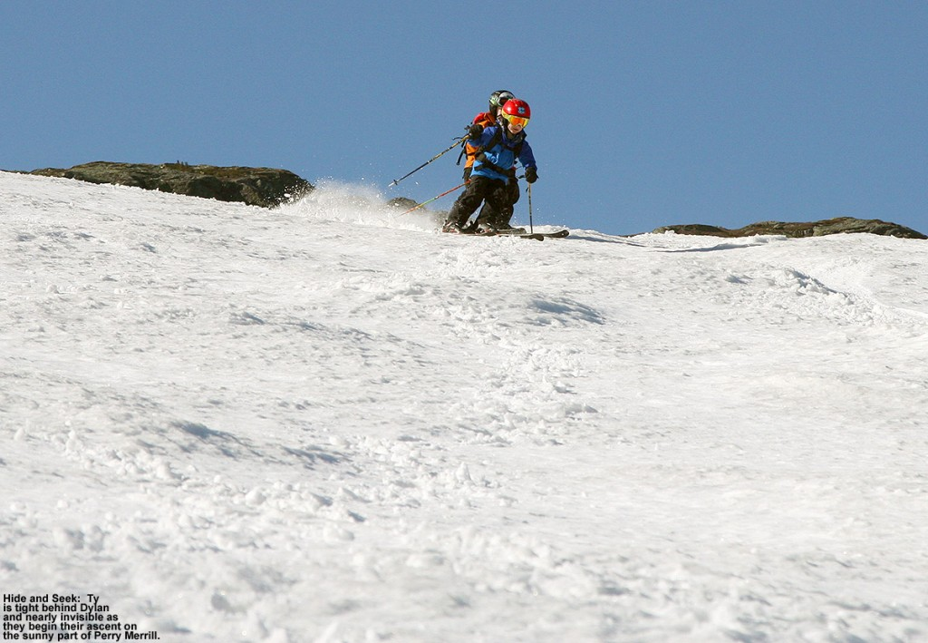 An image of Dylan with Ty mostly hidden behind as they begin a ski descent of the Perry Merrill trail at Stowe Mountain Ski Resort in Vermont