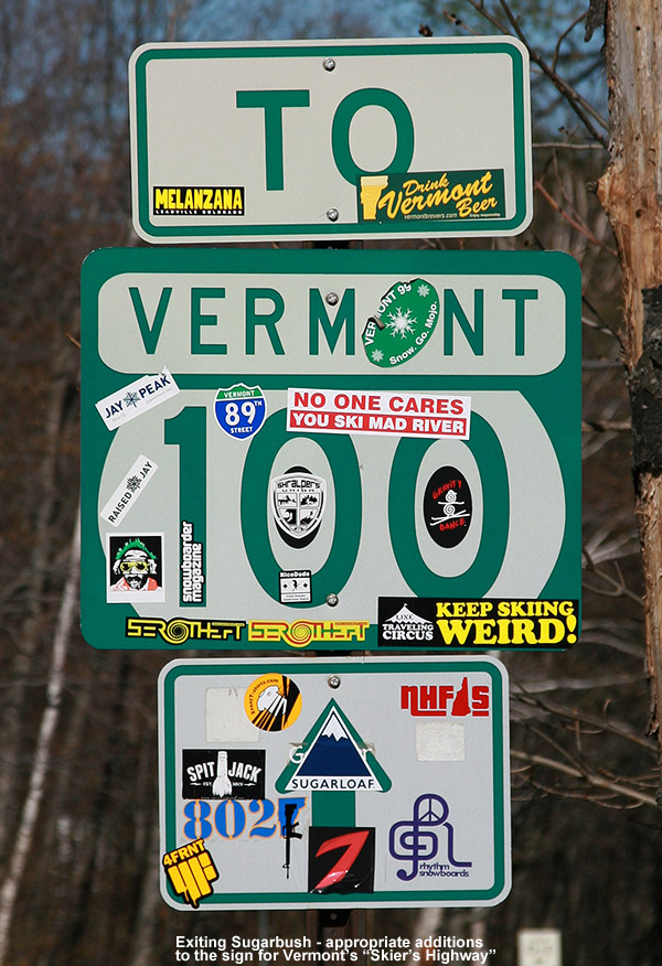 An image of a Route 100 highway sign in Vermont covered with a variety of ski stickers