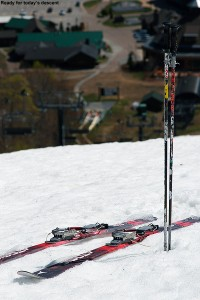 An image of skis and poles on the snow at the top of West Slope at Stowe Mountain Resort in Vermont looking down on the Spruce Peak Base area