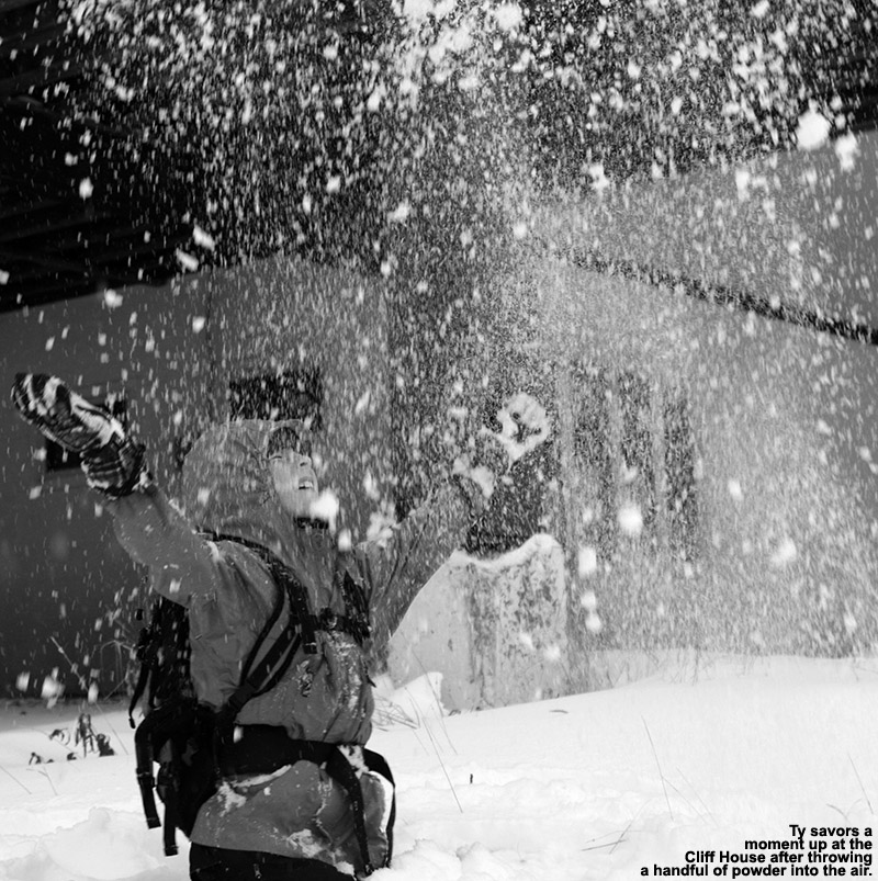 An image of Ty throwing a handful of October powder into the air at the Cliff House at Stowe Mountain Resort in Vermont
