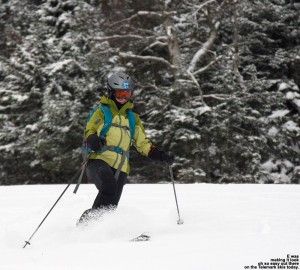 An image of Erica skiing in powder on the Perry Merrill trail at Stowe Mountain Resort in Vermont after some October snow