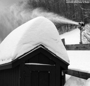 An image of snow on the roof of a shed with a snowgun in the background at Stowe Mountain Ski Resort in Vermont