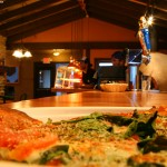 An image of a slice of pizza and the bar at the Fireside Flatbread restaurant at Bolton Valley Ski Resort in Vermont