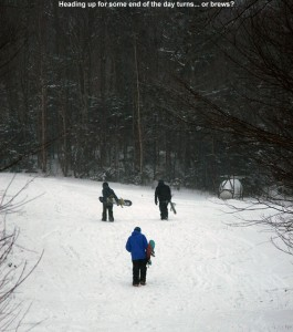 An image of snowbaorders hiking up the Lower Turnpike Trail at Bolton Valley Ski Resort in Vermont