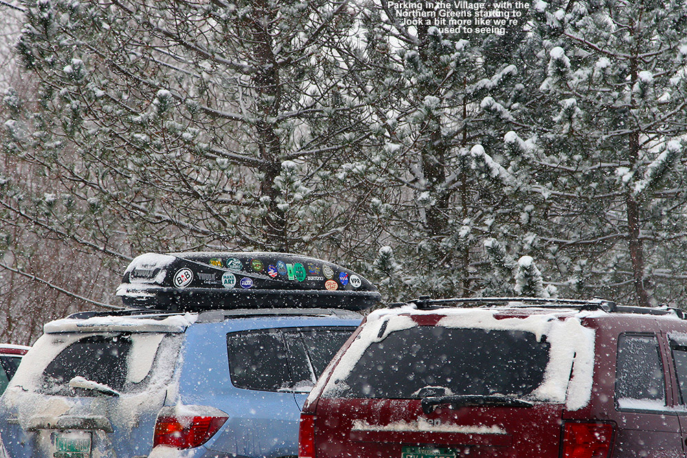 An image of ski vehicles and falling snow in the village parking lot at Bolton Valley Ski Resort in Vermont