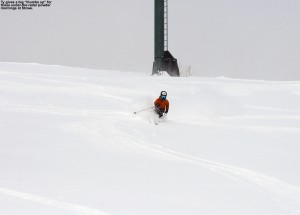 An image of Ty skiing powder in the open terrain above the Meadows trail at Stowe Mountain Resort in Vermont
