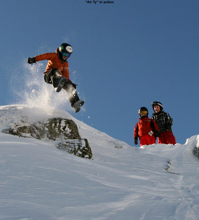 An image of Ty jumping off the ridge line of Mt. Mansfield above Stowe Mountain Resort in Vermont into powder below