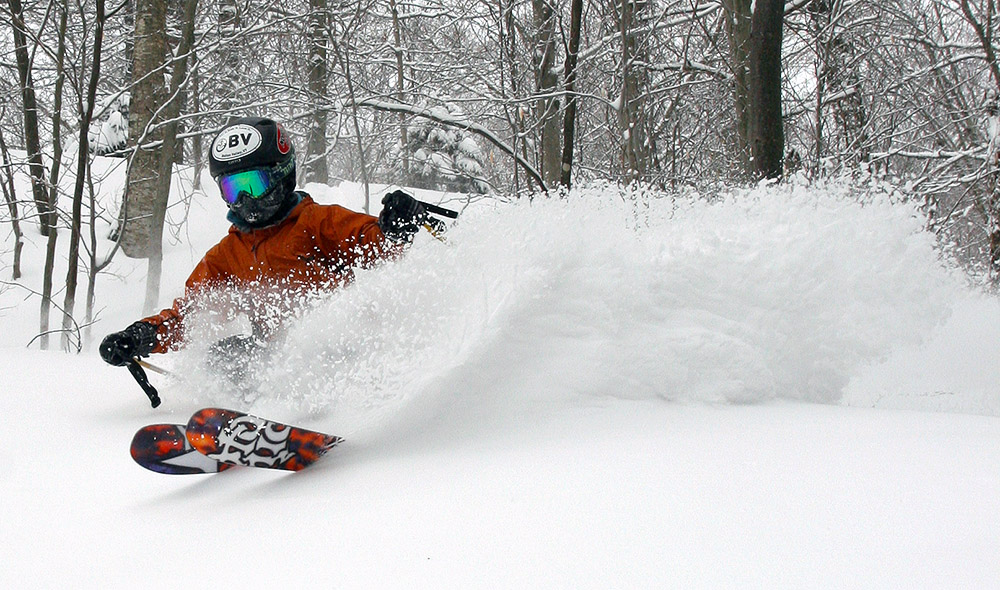 An image of Ty spraying powder while skiing in the trees on Mt. Mansfield at Stowe Mountain Resort in Vermont