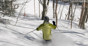An image of Erica skiing powder in the Lower Smugglers Trees at Stowe Mountain Resort in Vermont