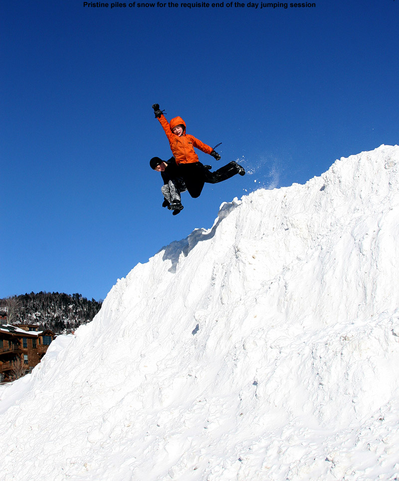 An image of Ty and Dylan jumping off a large snow pile at Stowe Mountain Ski Resort in Vermont