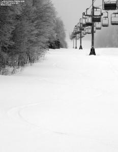 An image of a ski track in powder snow beneath the Wilderness Lift at Bolton Valley Resort in Vermont