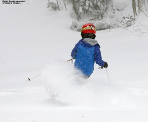 An image of Dylan skiing powder snow on the Duck Walk trail in April at Stowe Mountain Resort in Vermont