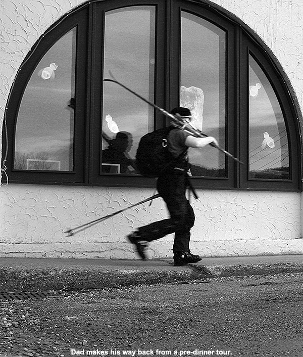 An image of Jay walking with Telemark skis in front of the base lodge at Jay Peak Ski Resort in Vermont