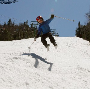 An image of Dylan jumping in the air on skis on the Jet Trail at Jay Peak Resort in Vermont