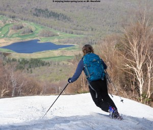 An image of Erica skiing on the slopes of Mt. Mansfield at Stowe Mountain Resort in Vermont in Mid May with an image of a pond and spring foliage in the background