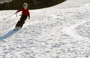 An image of Ty skiing in spring snow on the North Slope trail at Stowe Mountain Resort in Vermont in mid May