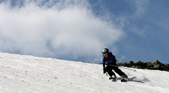 An image of Ty carving a turn on skis on the snowfields of Mt. Washington in New Hampshire in early June