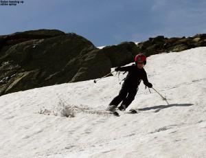 An image of Dylan skiing one of the snowfields on Mt. Washington in New Hampshire in June among some massive boulders