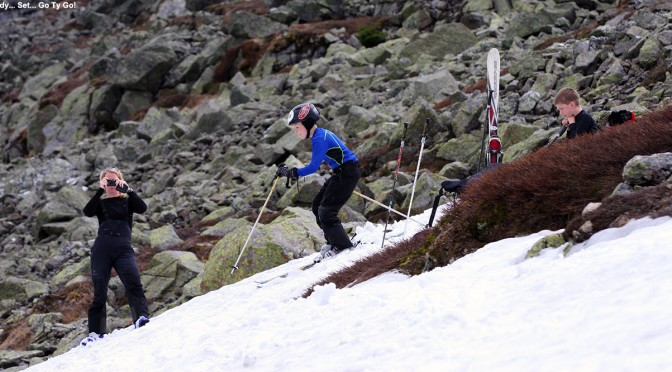 An image of Ty starting a run on one of the snowfields on Mt Washington in New Hampshire, with E taking pictures and Dylan looking on
