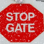 "An image of a frosty ""Stop Gate"" sign at the top of the Lookout Double Chairlift at Stowe Mountain Resort in Vermont"