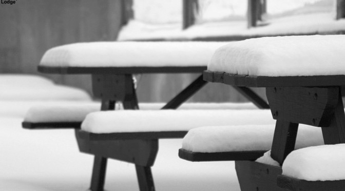 An image of snow on picnic tables at the Midway Lodge at Stowe Mountain Resort in Vermont