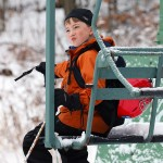 An image of Dylan sitting on the closed Wilderness Double Chairlift at the start of a ski tour at Bolton Valley Ski Resort in Vermont