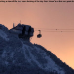 An image of the Jay Peak tram docking at its summit station back lit by light of the setting sun