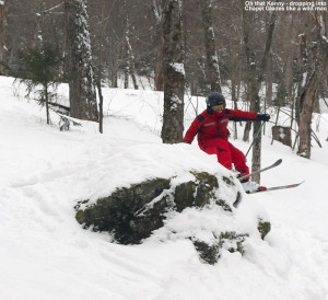 An image of Kenny jumping off a rock as he skis in the Chapel Glades at Stowe Mountain Resort in Vermont