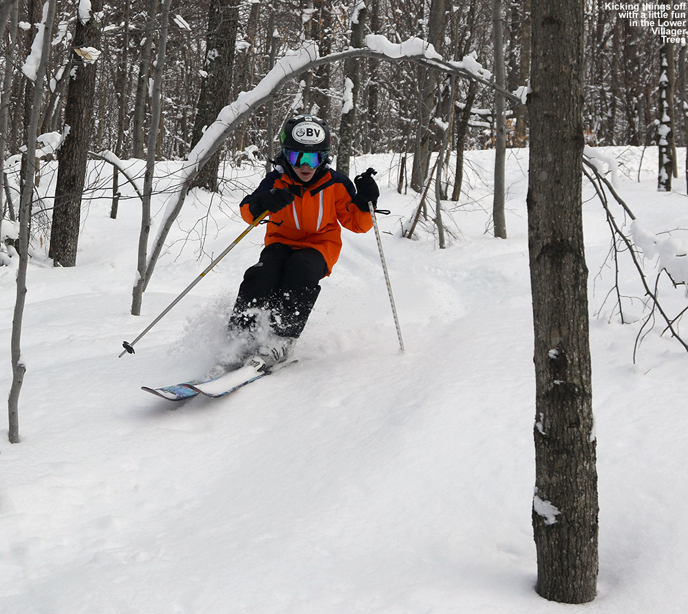 An image of Ty skiing udner and arched tree in the Lower Villager Trees at Bolton Valley Ski Resort in Vermont