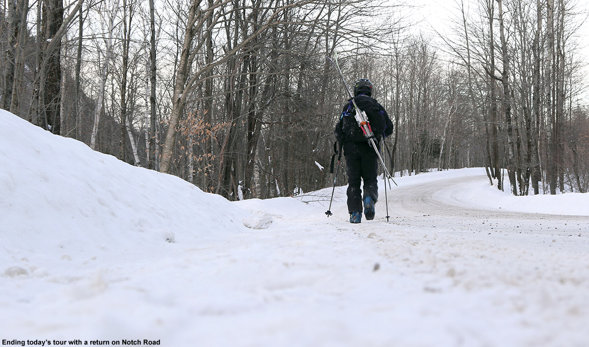 An image of Jay hiking with skis his pack on Bolton Notch Road in Vermont to return to his car