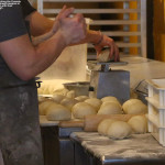 An image showing the cooks at Fireside Flatbread pizza at Bolton Valley Ski Resort as they prepare balls of dough for the pizza crusts