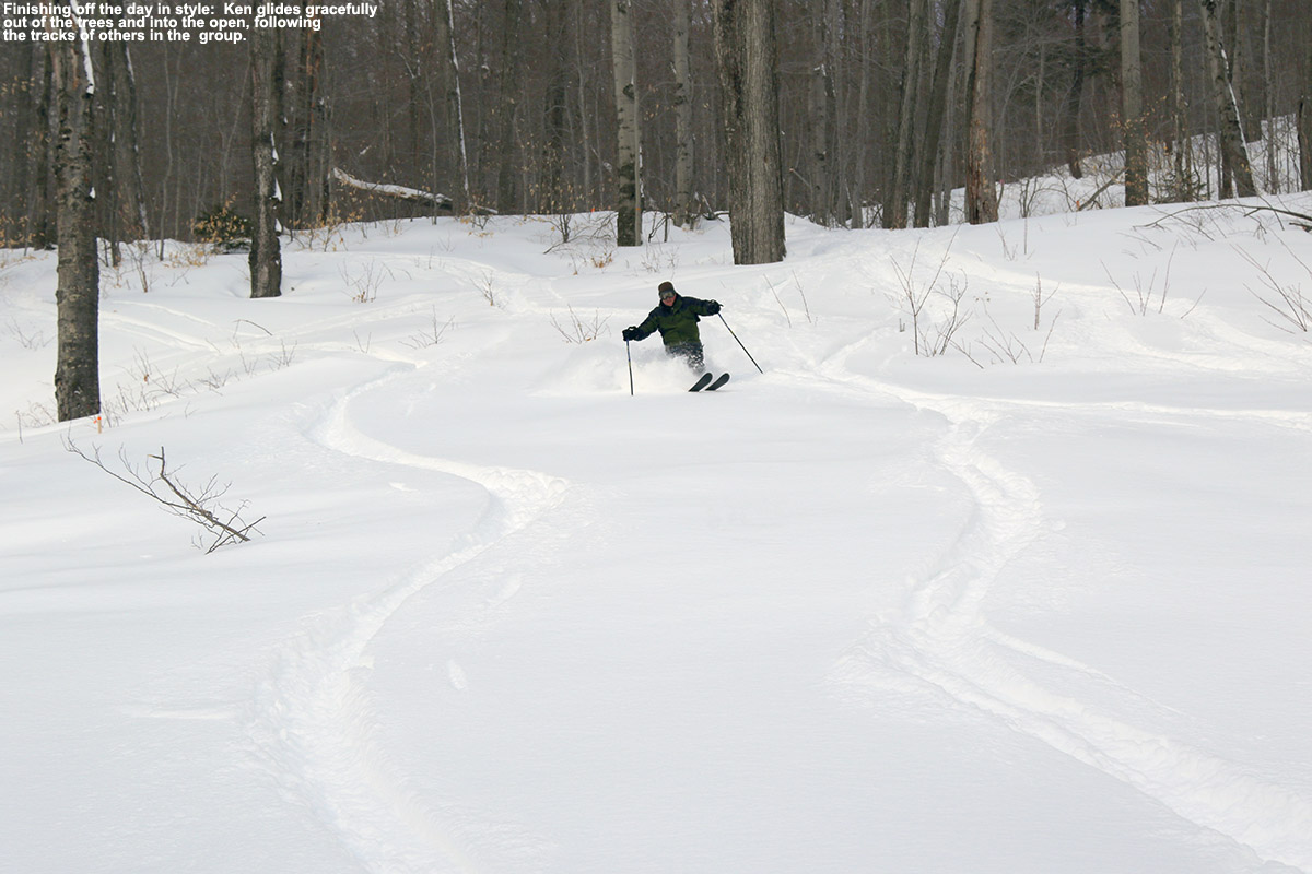 An image of Ken skiing dry powder as he comes out of the trees and into the open on Spruce Peak at Stowe Mountain Resort in Vermont