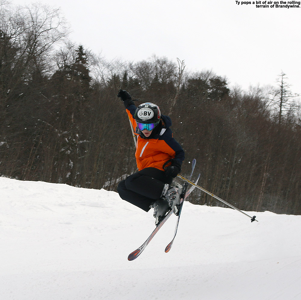 An image of Ty doing a jump on skis on the Brandywine trail at Bolton Valley Ski Resort in Vermont