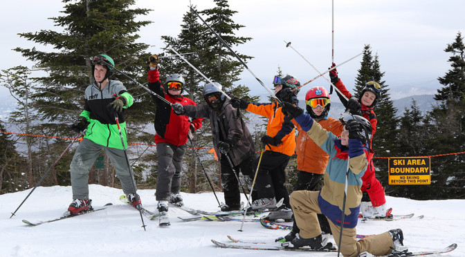 An image of students from the Bishop John A Marshall School raising their ski poles as they get ready for a run down the Bruce Trail outside the boundaries of Stowe Mountain Ski Resort in Vermont