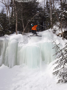 An image of Ty jumping off a large frozen waterfall on skis at Stowe Mountain Resort in Vermont