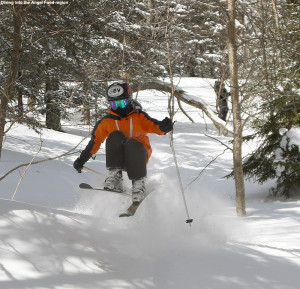 An image of Ty doing a jump while skiing powder at Stowe Mountain Resort in Vermont