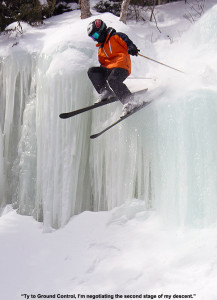 An image of Ty bouncing off the second tier of an ice waterfall in the trees near Angel Food at Stowe Mountain Resort in Vermont