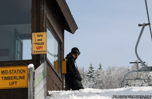 An image of a lift attendant watching the chairs pass by on the Bolton Valley Timberline Mid Station
