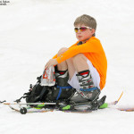An image of Dylan sitting on the snow at the start of spring skiing ascent at Stowe Mountain Resort in Vermont