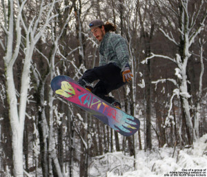 An image of a snowboarder jumping at Stowe Mountain Resort in Vermont