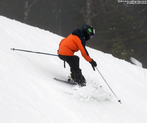 An image of Ty carving a turn and pushing some soft snow on the Liftline trail at Stowe Mountain Resort in Vermont