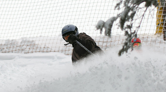 An image of Wiley spraying powder snow while he skis in the Cliff Trail trees at Stowe Mountain Resort in Vermont