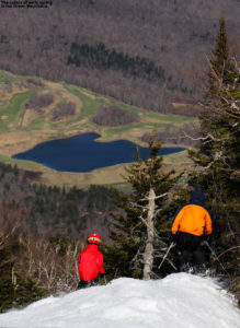 An image of skiers above the valley in spring at Stowe Mountain Resort in Vermont