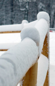 An image of fresh snow on a fence in the Village at Bolton Valley Ski Resort in Vermont
