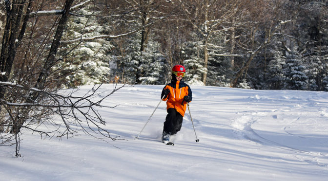 An image of Dylan skiing powder snow in the Wilderness area at Bolton Valley Resort in Vermont